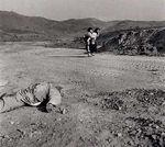 A Korean woman carries a child past a dead ROK soldier.